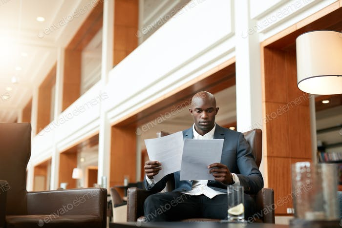 Business executive at lobby reading documents