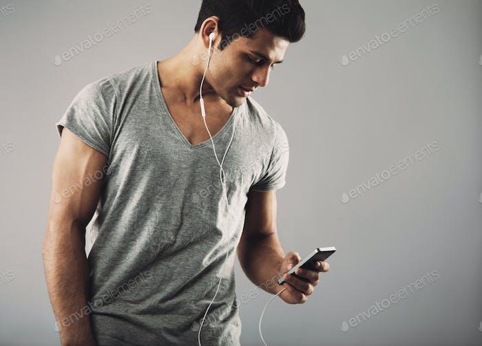 Young guy enjoying listening music on smartphone