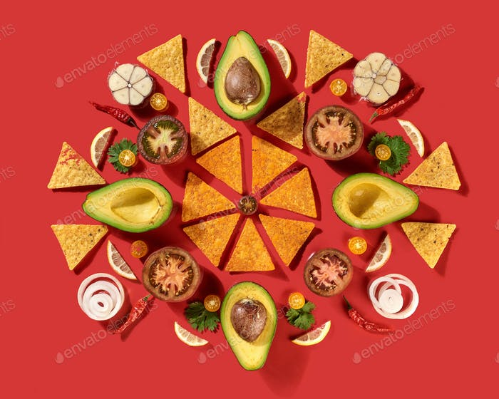 Mexican corn nachos chips, avocado, lemon, garlic, tomato, onion, parsley green as a round pattern -