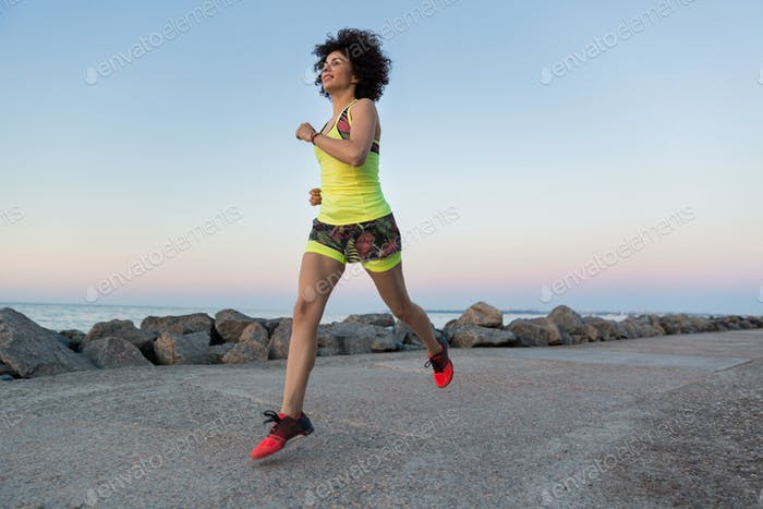 Healthy sportswoman running outdoors at the beach