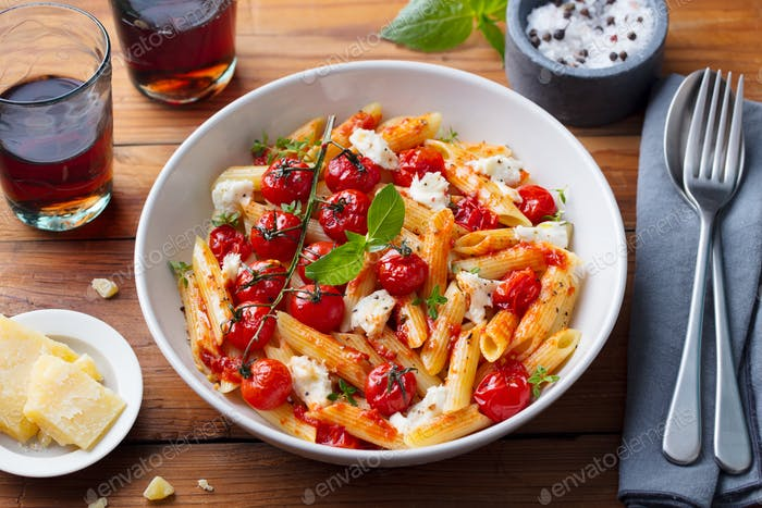 Pasta Penne with Roasted Tomato, Sauce, Mozzarella Cheese. Wooden Background.