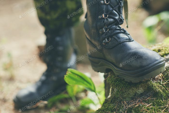 close up of soldier feet with army boots in forest