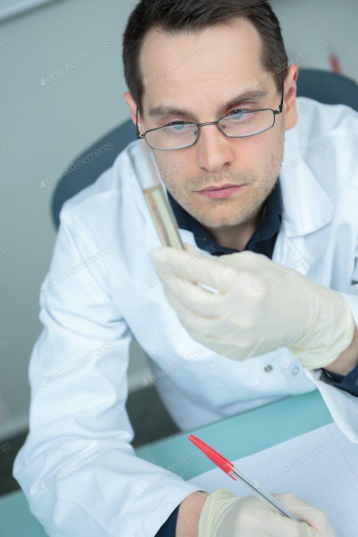 Wissenschaftler Blick auf Glasröhre im Labor