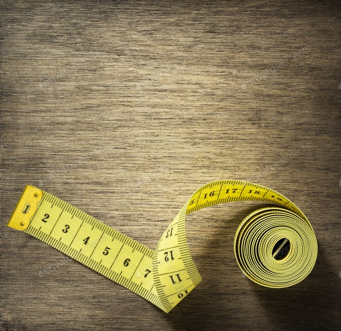 measuring tape on wooden background