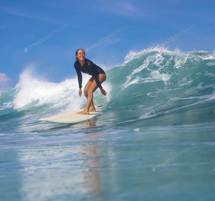 Female surfer on a blue wave