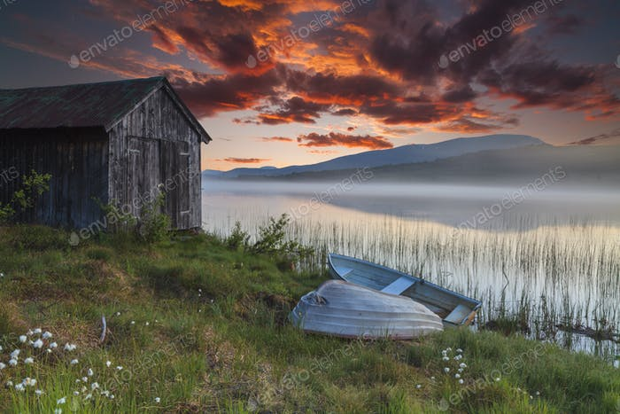 View on foggy lake with boats on the shore. Norway