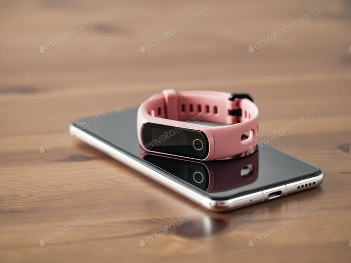 Fitness tracker on smartphone wooden tabletop