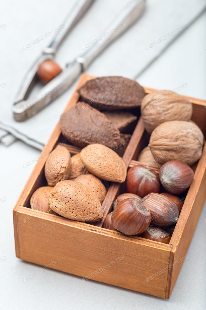 Hazelnut, walnut, almond and brazil nuts in the wooden box with nut cracker