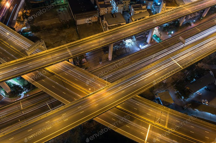 Top view of massive expressway at night with light of cars, transportation industrial concept