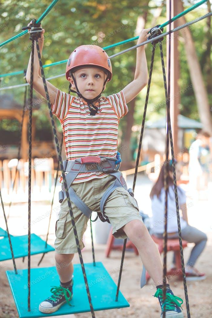 little boy make climbing in the adventure park.