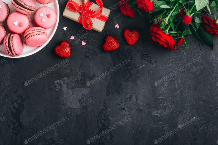 Valentines day background with pink macarons, red roses, present box and red hearts