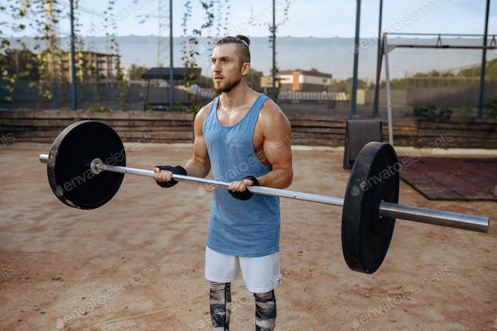 Strong man doing exercise with barbell, workout