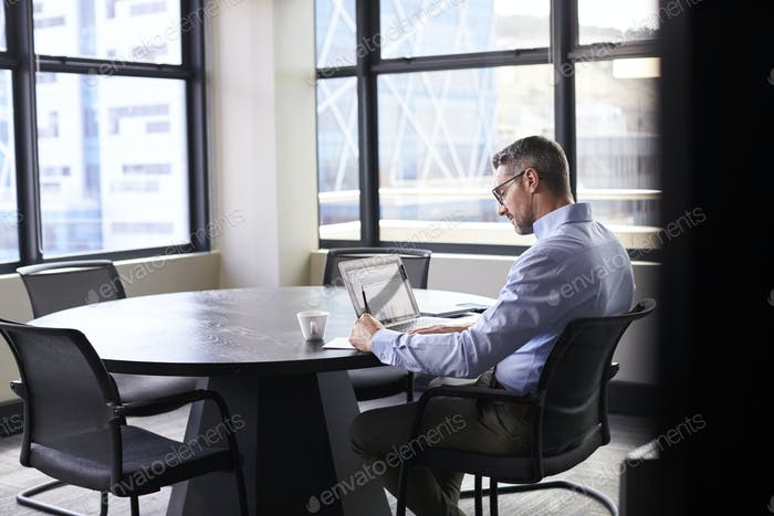 Middle aged white businessman working alone in a meeting room, seen from doorway