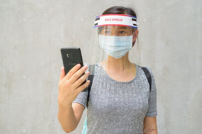 Young Asian woman using phone with mask and face shield for protection from corona virus outbreak