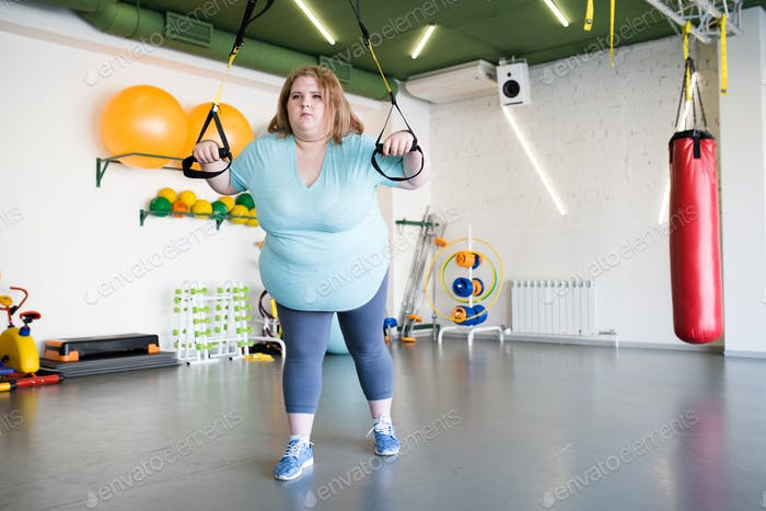Overweight Woman Using Machines  in Gym