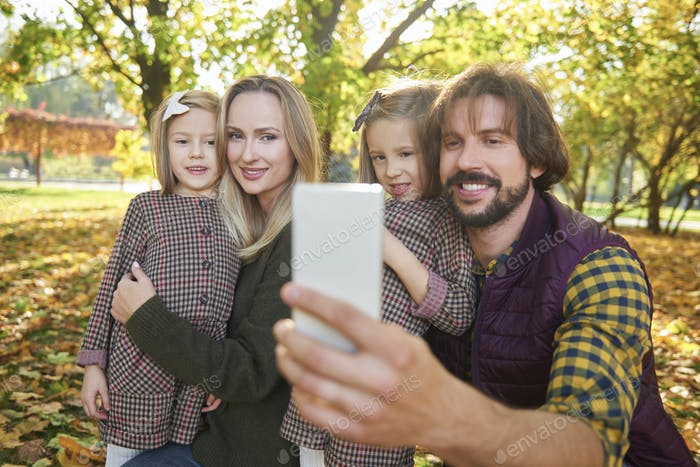 Happy family making a selfie in autumn forest