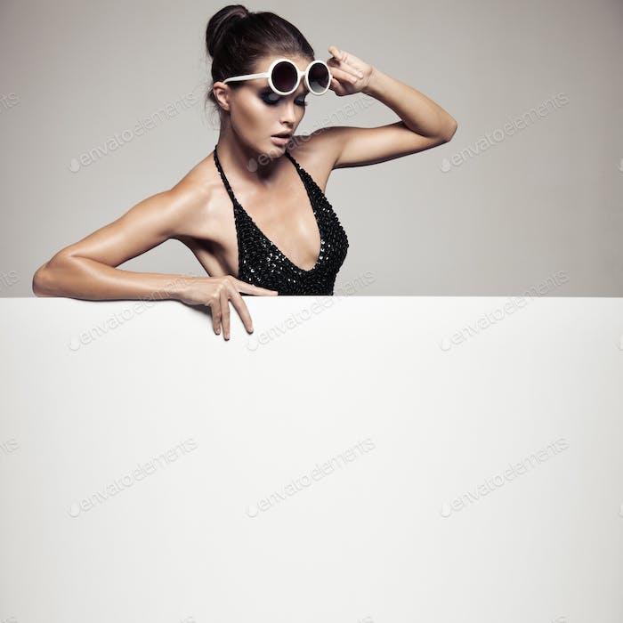 Schöne Frau in schwarz Bikini halten Big Leere Plakatwand