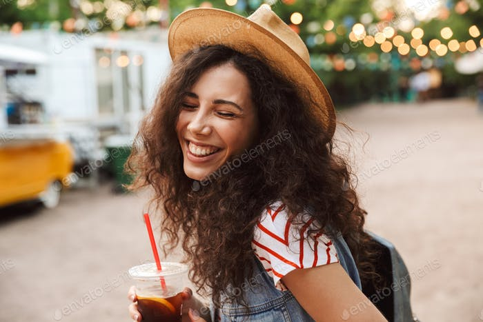 Photo of joyful cute woman 18-20 with curly brown hair wearing s