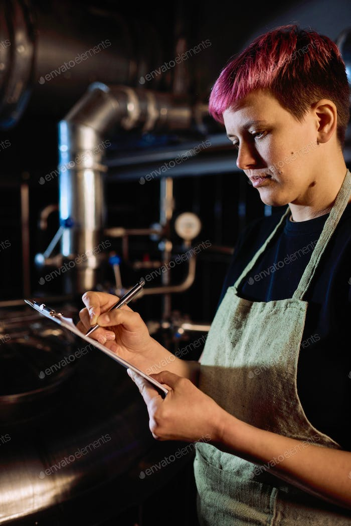 Young serious female brewer in apron pointing at document in clipboard