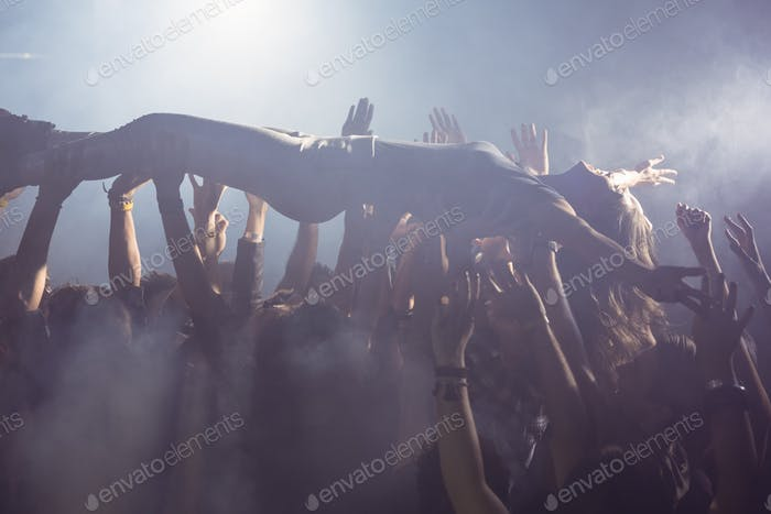 Cheerful crowd lifting female performer at nightclub