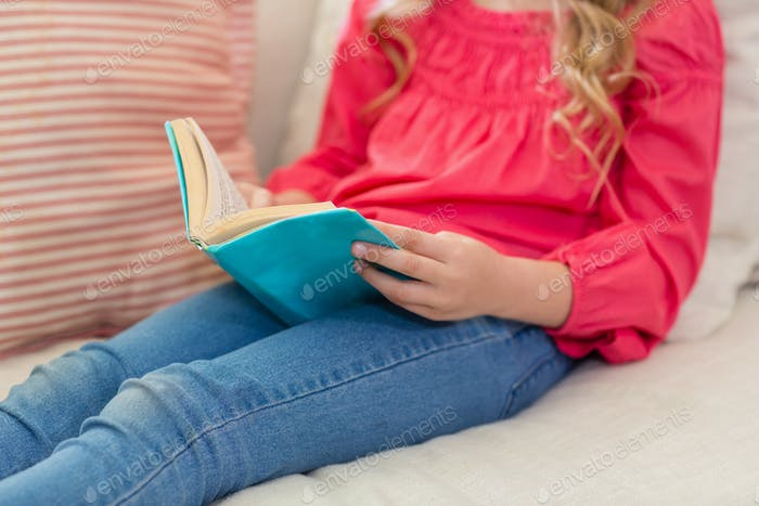 Girl reading a book on sofa in living room