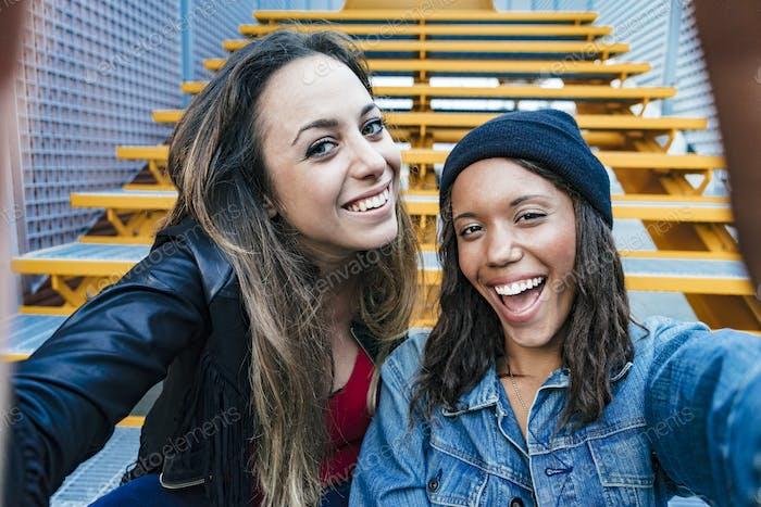 dos mixta raza hembra amigos sentado y tomando un selfie