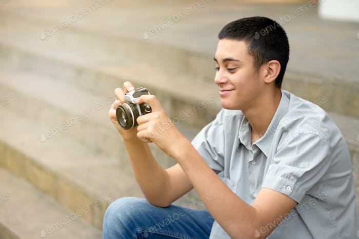 Young teenage boy smiling as he checks his camera