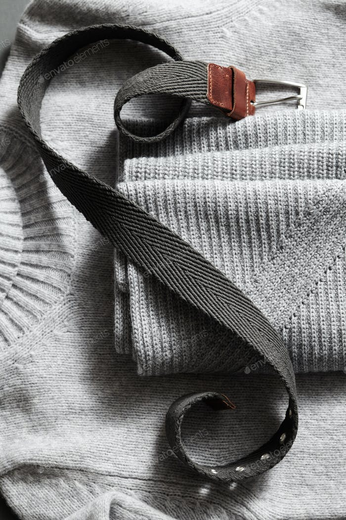 leather belt on background knit gray sweater