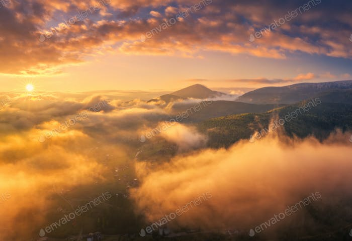 Mountains in low clouds at sunrise in summer. Aerial view