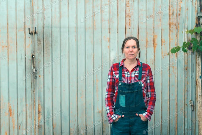 Portrait of beautiful female farmer in front of farmhouse shed