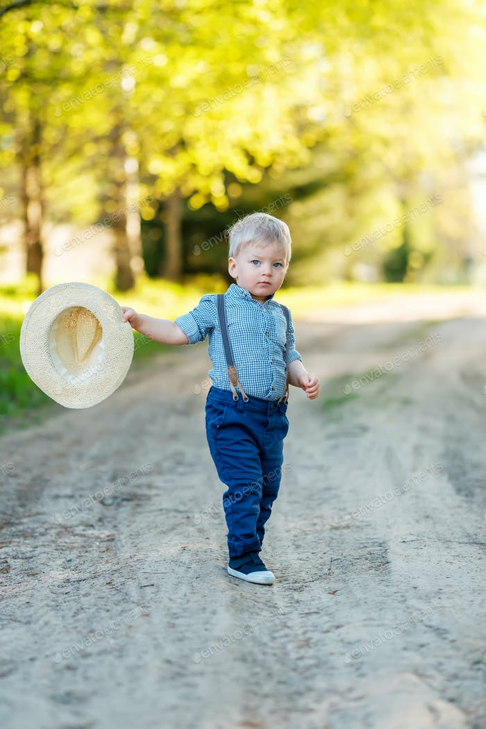 Toddler child outdoors. Rural scene with one year old baby boy with straw hat