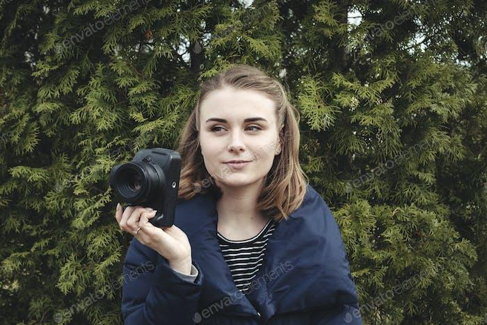 Attraktive lächelnde Fotograf hält ihre Kamera
