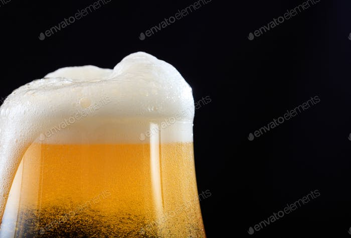 A glass of beer detail on black background, copy space