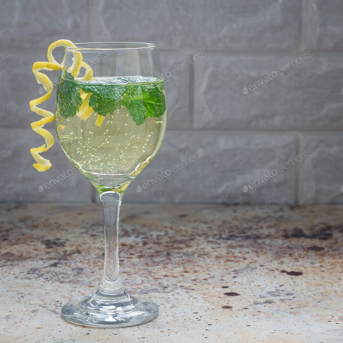 Spritzer cocktail with white wine, mint and ice, decorated with spiral lemon zest, square format