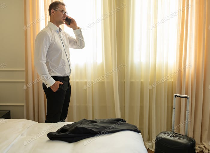 Adult businessman talking on phone in hotel