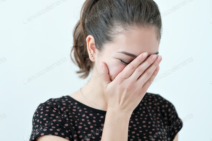 Playful shy woman hiding face with her hands