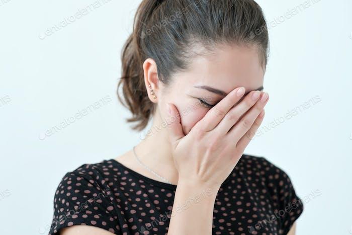 verspielt schüchtern Frau versteckt Gesicht mit ihren Händen