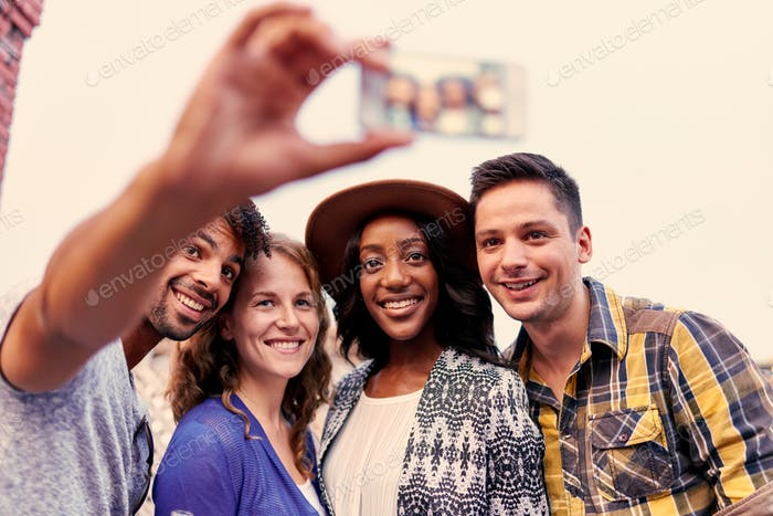 Multi-ethnic millenial group of friends taking a selfie photo wi