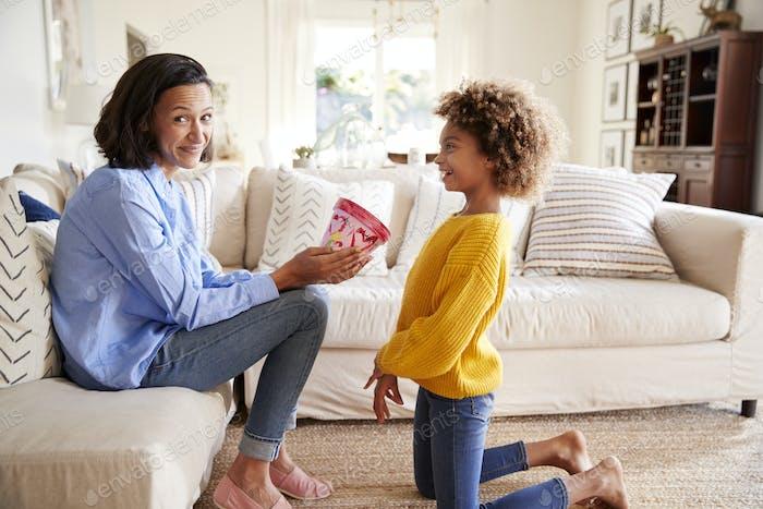pre-teen Mädchen kniend und geben ihre Mutter ein hausgemachte dekoriert Blumentopf