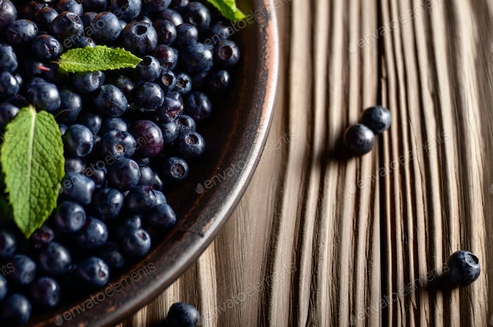 Clay plate full of Ripe organic blueberries on wooden table