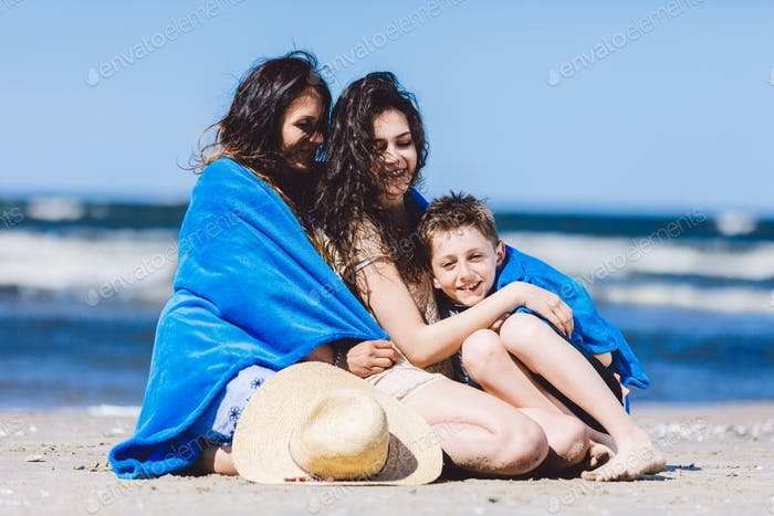 Mother and her children wrapped in a blanket by the sea.