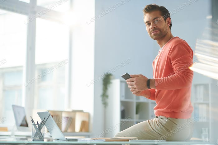 Young casual businessman with smartphone looking at you