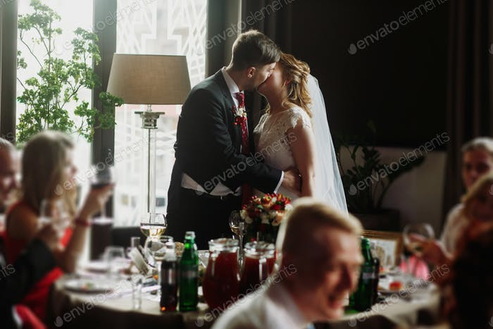 Newlywed couple kissing at wedding reception in restaurant