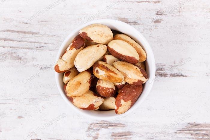 Brazil nuts in glass bowl on rustic board
