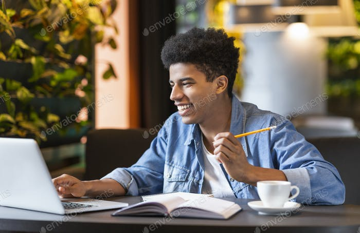 Creative teenaged guy working on project at cafe