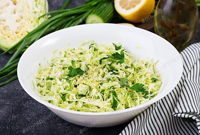 Healthy salad. Spring vegan salad with cabbage, cucumber, green onion and parsley on dark table.