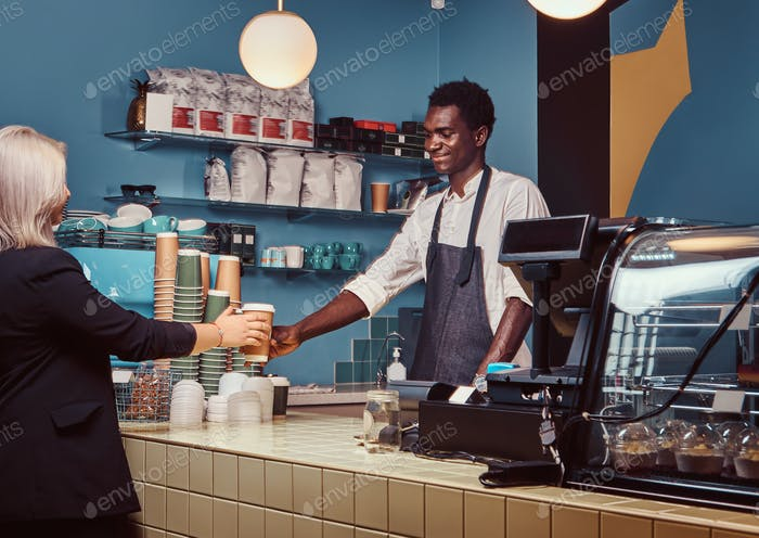 African American barista in uniform giving a cup of coffee to his client at the trendy coffee shop