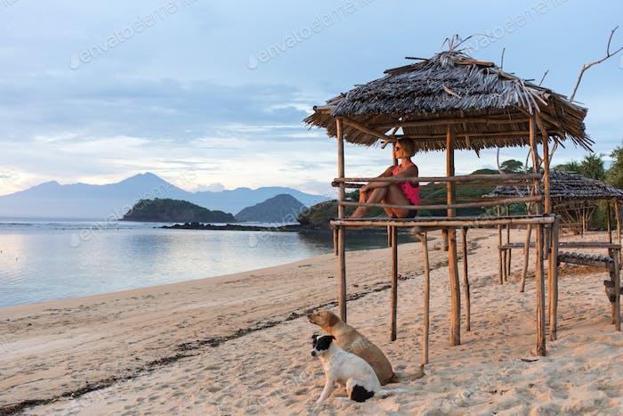 joyful nice woman or girl sitting on sandy beach