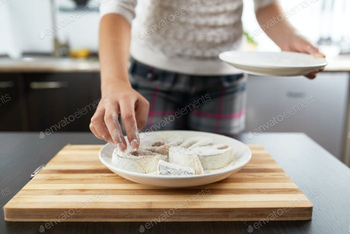 girl rolls fish in flour to fry
