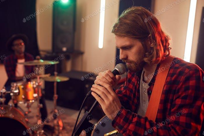 Schöner junger Mann singt in studio